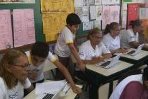 Crianças ajudam estudantes da EJA a manusearem computadores